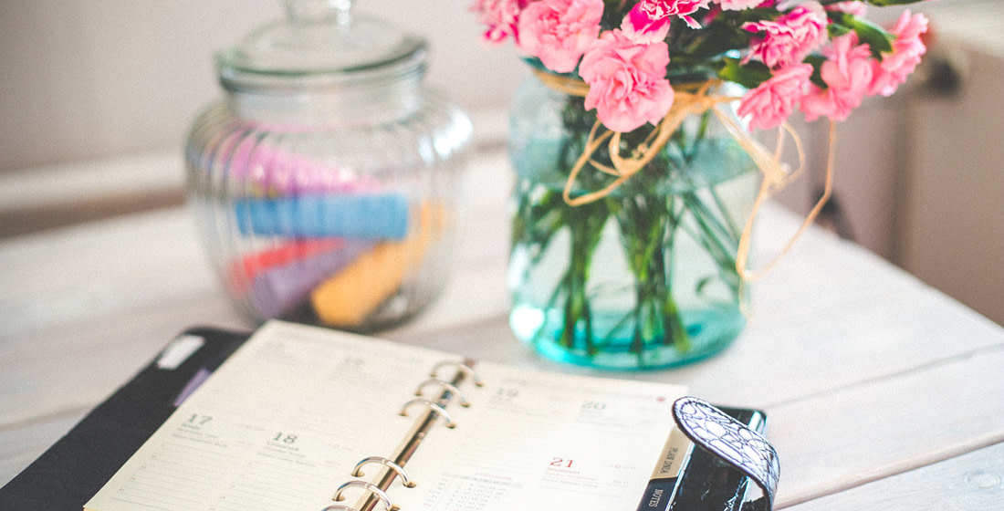 notebook in front of glass flower pot