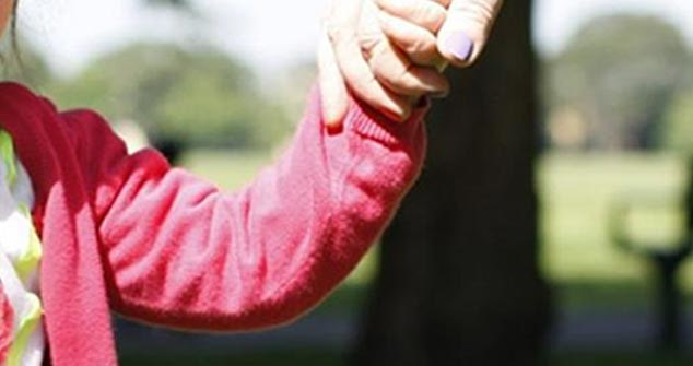 parent holding hand of child